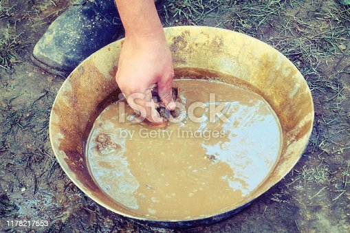 Historical reconstruction of prospector by hand, retro. A man stands next to a tray for washing gold sand. Washing of gold in tray by American settlers in Alaska.