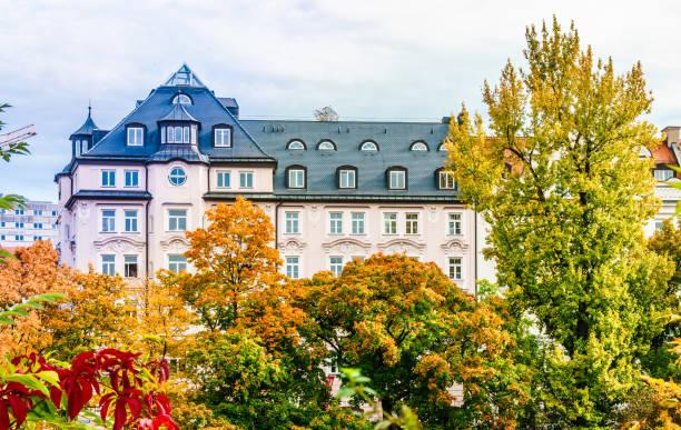 historische wohngebäude vor colorfull bäume im herbst in münchen-city - arbeit in münchen stock-fotos und bilder