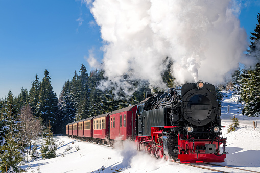 Historical steam train running full speed to Brocken Mountain in Harz region