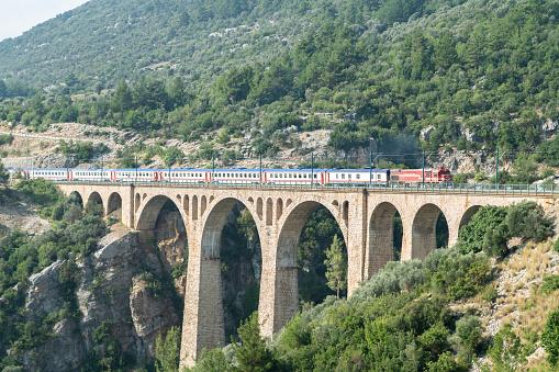 Adana, Turkey - August 31, 2019 : Historical Varda Bridge in Adana, Turkey. Train passing over railroad.