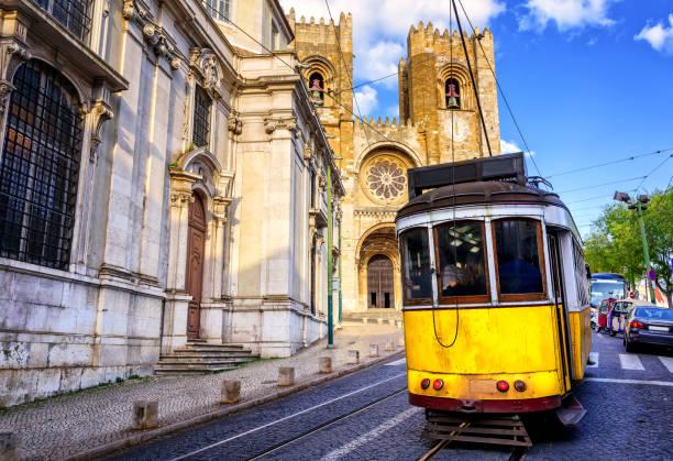 historical yellow tram in front of the lisbon cathedral, lisbon, portugal - eletrico lisboa imagens e fotografias de stock