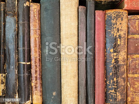 Historically valuable books. Very old and torn books on the shelf. Collection editions of books