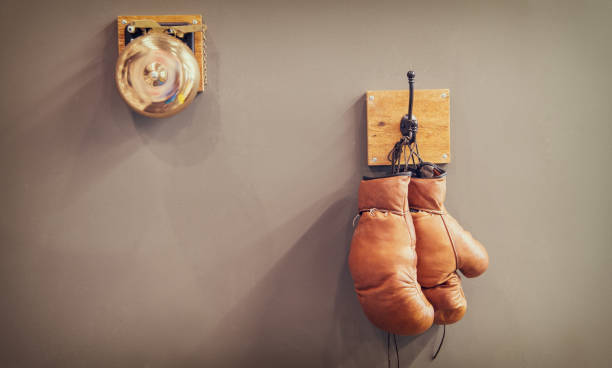 history of sport. vintage gong and worn gloves. stamina. final gong in battle retro boxing gloves. vintage sport equipment. boxing concept. old boxing gloves on hanger. copy space. Final sparring stock photo