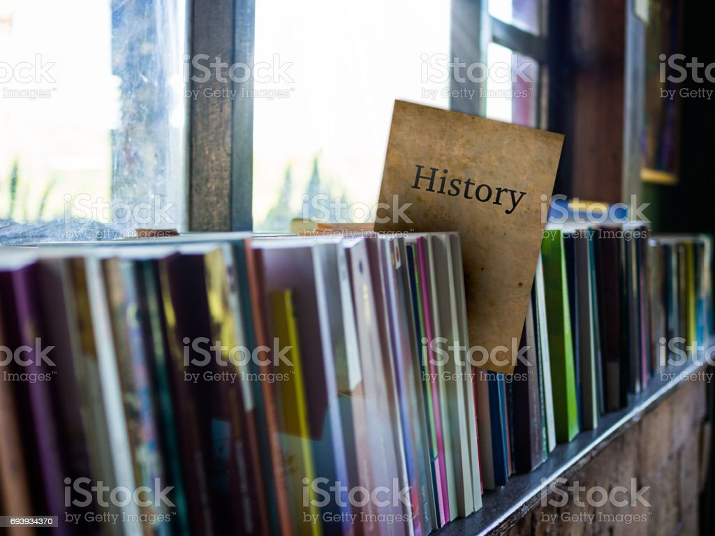 History on book cover on bookshelf, education concept