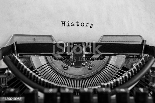 istock History typed on an vintage typewriter, old paper. 1159049987