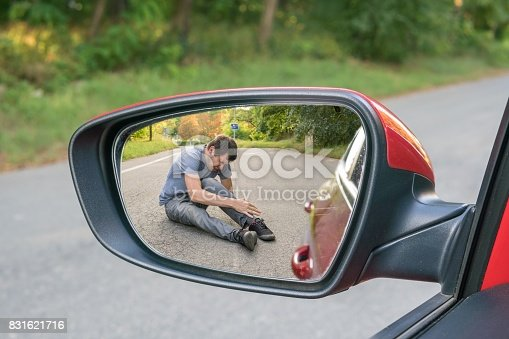 istock Hit and run concept. View on injured man on road in rear mirror of a car. 831621716