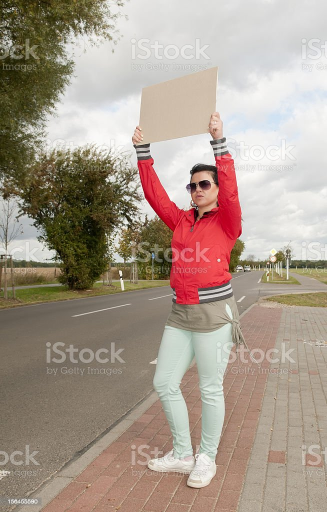Hitchhiker with blank sign royalty-free stock photo