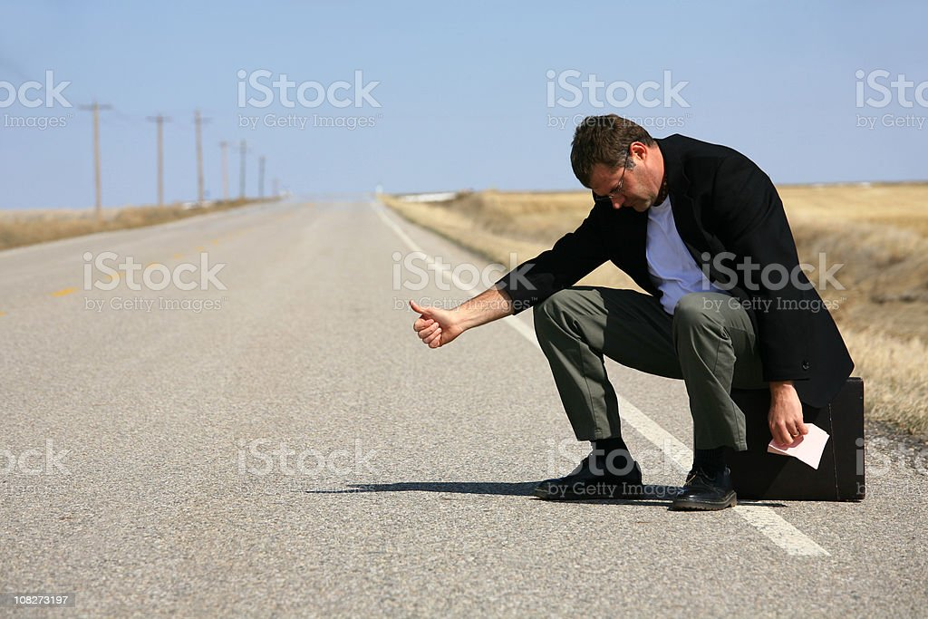 Hitchhiking Caucasian Businessman Holding Pink Slip royalty-free stock photo