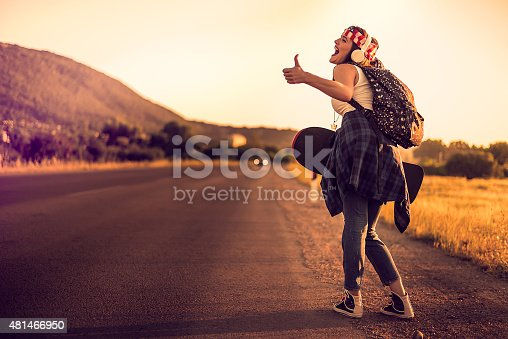 Young hipster with headphones,backpack and skateboard hitchhiking on the road