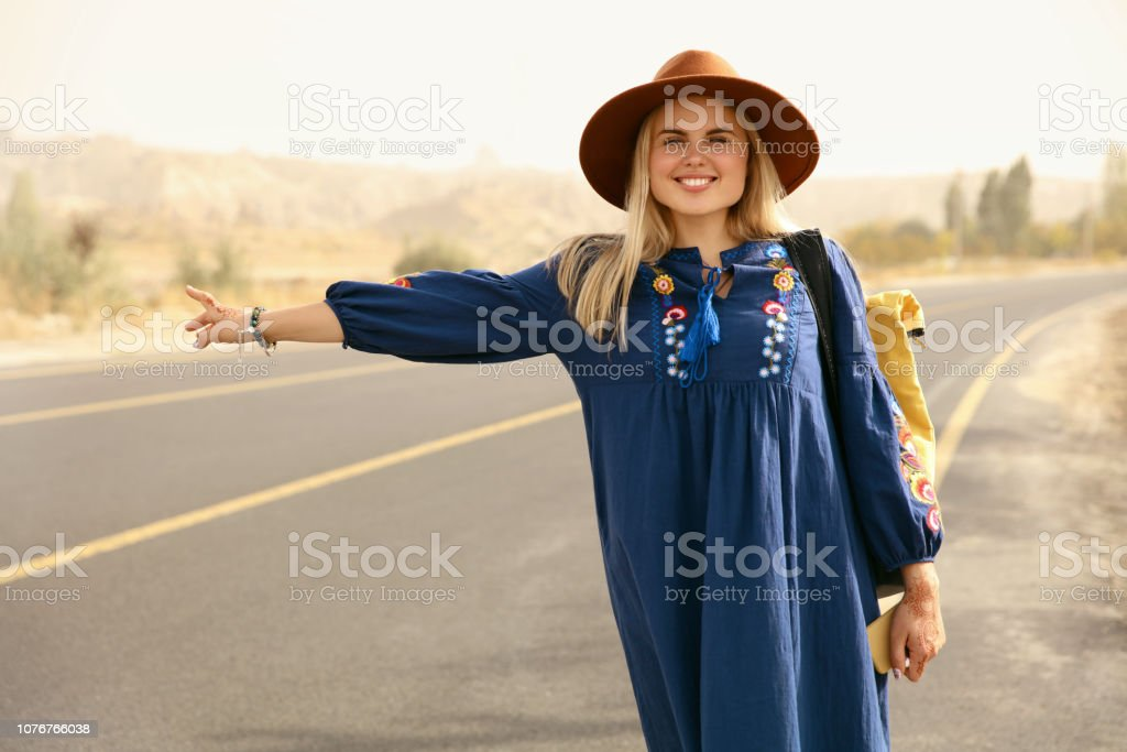Hitchhiking Travel. Woman Trying Stop Transport On Highway stock photo