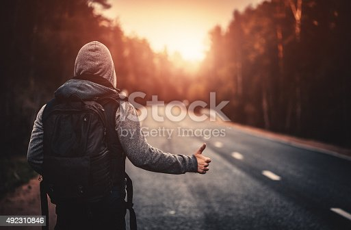 Hitchhiking traveler with backpack trying to stop the car on road in the forest at sunset. Stock photo.