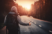 istock Hitchhiking traveler trying to stop the car on road 492310846