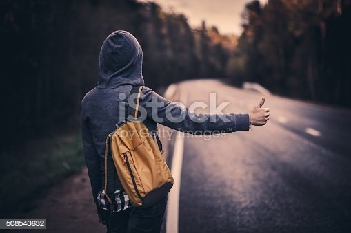 Hitchhiking traveler with backpack trying to stop the car on road in the forest. Stock photo.
