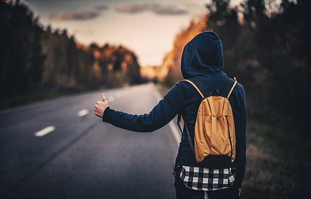 Hitchhiking traveler trying to stop the car on road stock photo