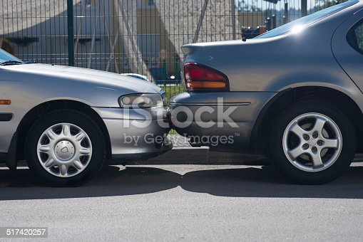 Hitting into a parked car while parking a vehicle in a parallel line parking space.