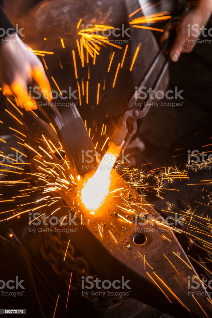 Hitting Molten Iron With a Hammer on Anvil, with Sparks Flying stock photo