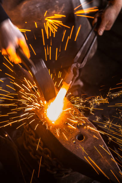 Hitting Molten Iron With a Hammer on Anvil, with Sparks Flying Hitting Molten Iron With a Hammer on Anvil, with Sparks Flying anvil stock pictures, royalty-free photos & images