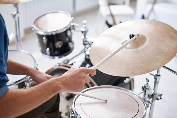 Hitting on drums Close-up of male hand hitting drums with sticks drum kit stock pictures, royalty-free photos & images