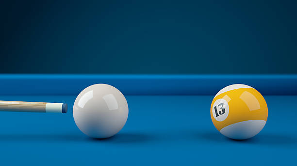 hitting the cue ball number 13 on a blue billiard ball - pool cue stock photos and pictures
