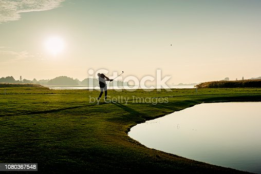 Golfer hitting a delicate wedge shot over a water feature and towards the flag. Photographed in the late autumn light on a course on the island of Møn in Denmark. Colour, horizontal with some copy space.