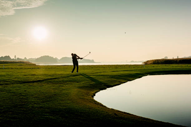 Hitting the perfect pitch shot. Golfer hitting a delicate wedge shot over a water feature and towards the flag. Photographed in the late autumn light on a course on the island of Møn in Denmark. Colour, horizontal with some copy space. green golf course stock pictures, royalty-free photos & images