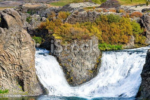 istock Hjalparfoss waterfall landscape closeup of orange and red tree foliage in south Iceland in autumn fall season with nobody and water falling 1131402693