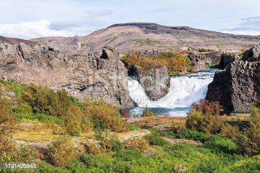 istock Hjalparfoss waterfall landscape of orange green tree foliage in southern Iceland in autumn fall season and water falling 1131405943