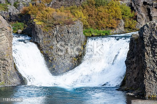 istock Hjalparfoss waterfall landscape of orange tree foliage in south Iceland in autumn fall season closeup with nobody and water falling 1131404382