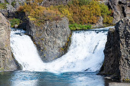 1131408581 istock photo Hjalparfoss waterfall landscape of orange tree foliage in south Iceland in autumn fall season closeup with nobody and water falling 1131404382