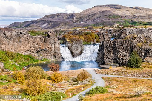 istock Hjalparfoss waterfall landscape of orange tree foliage in south Iceland in autumn fall season with water falling and highway road 32 and trail path hiking 1131407443