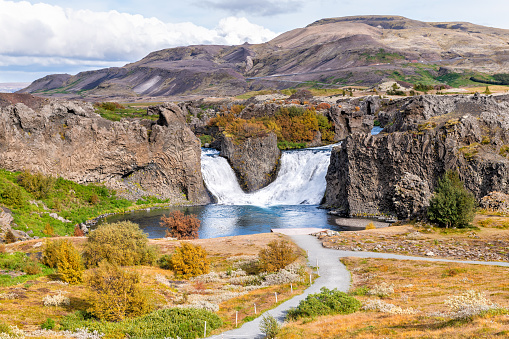 1131408581 istock photo Hjalparfoss waterfall landscape of orange tree foliage in south Iceland in autumn fall season with water falling and highway road 32 and trail path hiking 1131407443