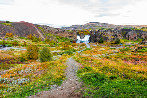 1131408581 istock photo Hjalparfoss waterfall landscape wide angle view of orange green foliage trail path in southern Iceland golden circle in autumn fall season 1204283618
