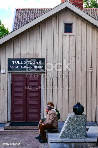 Hjo, Sweden July 8, 2020 A senior couple sit in front of the old Toll House, an antique shop