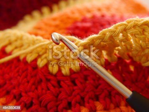 Eine Häleldecke. Nahaufnahme einer Häkelnadel mit Wolle in verschiedenen warmen Rottönen.