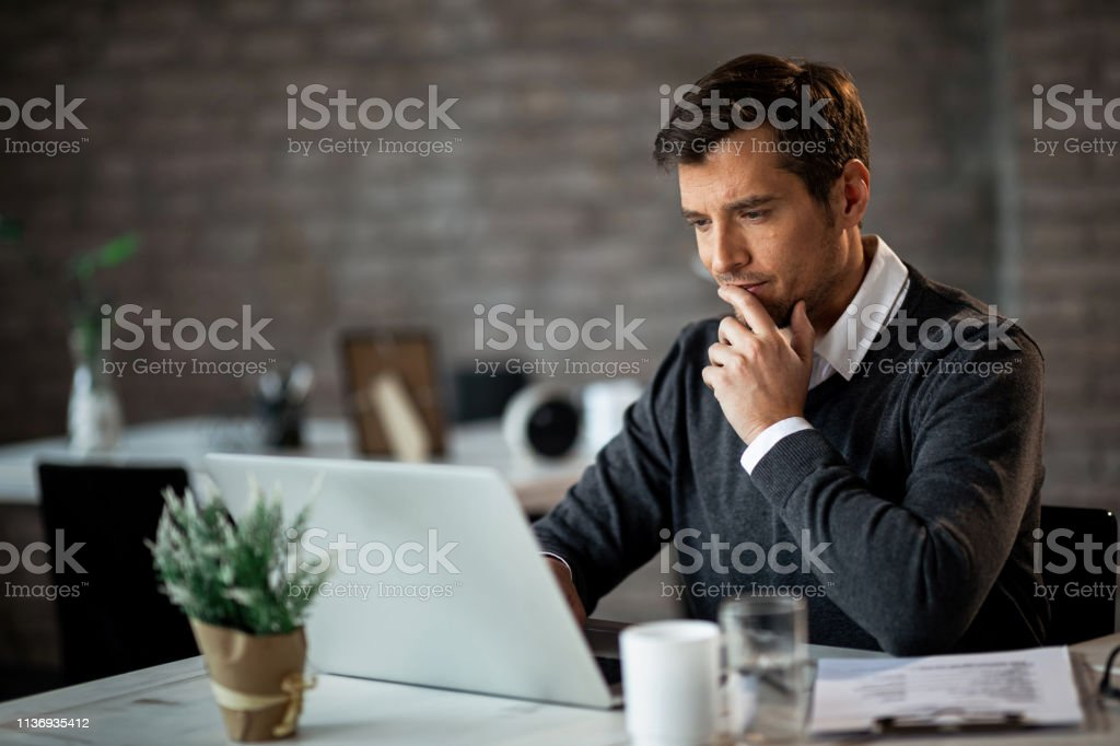 Hm, this is an very interesting e-mail! Smiling businessman using laptop and contemplating while working at his desk in the office. Adult Stock Photo