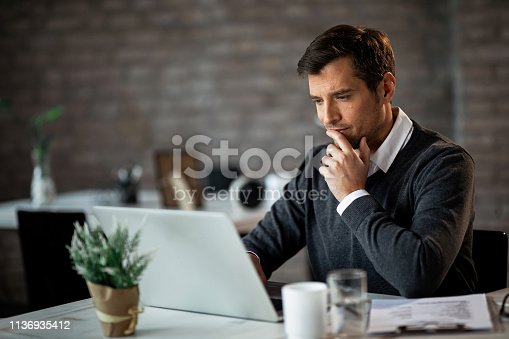 Smiling businessman using laptop and contemplating while working at his desk in the office.