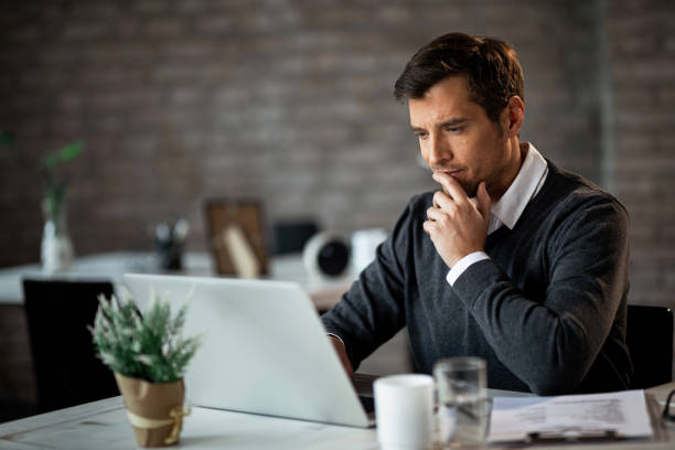 Hm, this is an very interesting e-mail! Smiling businessman using laptop and contemplating while working at his desk in the office. reflection stock pictures, royalty-free photos & images