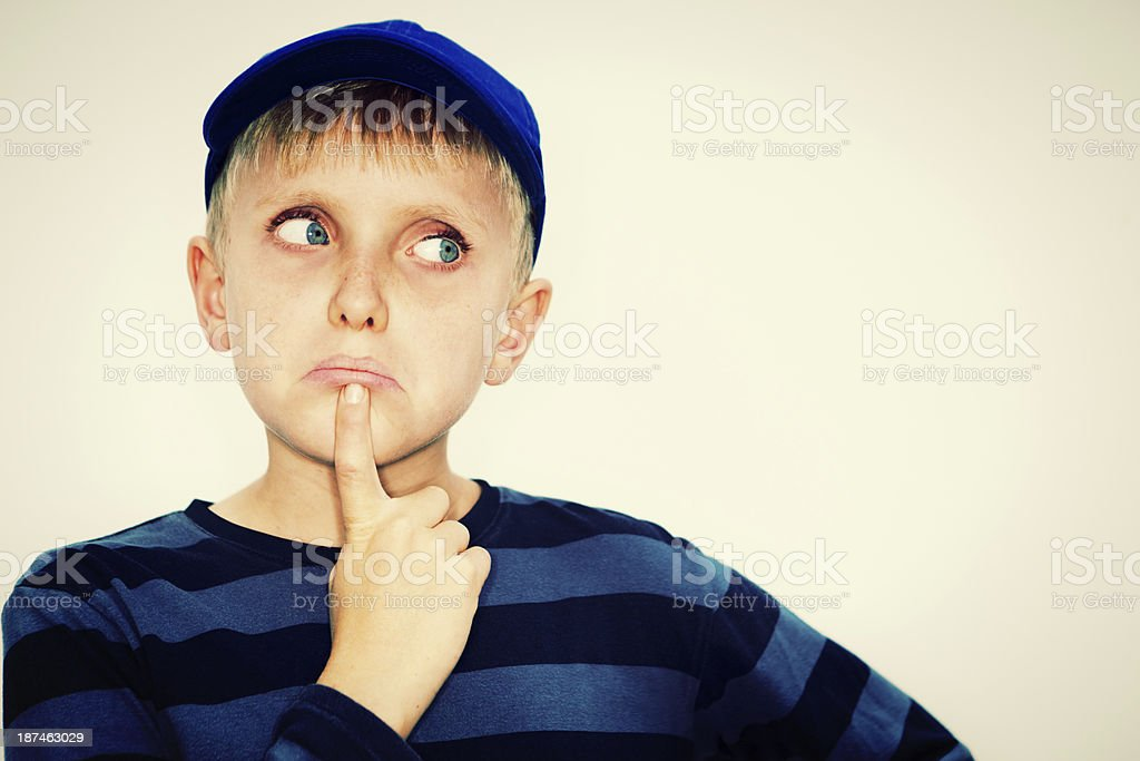 Hmm, not sure! Blond boy looks to side, undecided stock photo