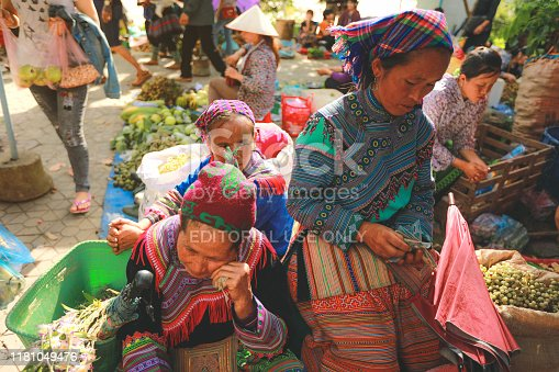Sapa, Vietnam - July 7, 2019 : Hmong women selling vetgetable in Bac Ha market, Northern Vietnam. Bac Ha is hilltribe market where people come to trade for goods in traditional costumes
