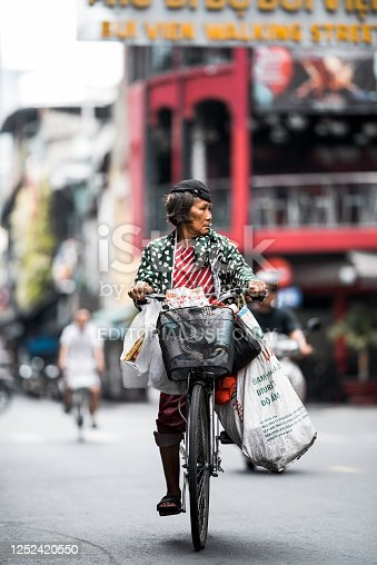 Ho Chi Minh, Vietnam - 9.06.2020. Vietnamese woman is going down the street by bicycle with bags. High quality photo