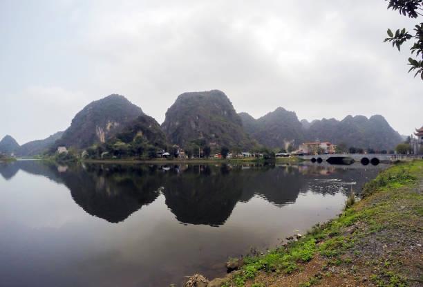 hoa lu tempel, brücke und see, umgeben von kalksteine - ninh binh province, vietnam, asien - holu stock-fotos und bilder