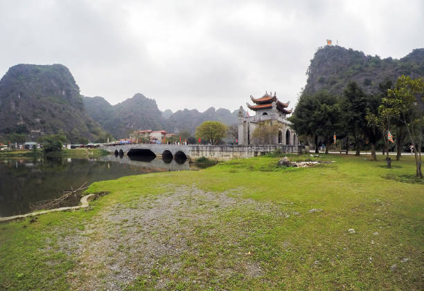 hoa lu tempel, brücke, see und eingang tor, umgeben von kalksteine - ninh binh province, vietnam, asien - holu stock-fotos und bilder