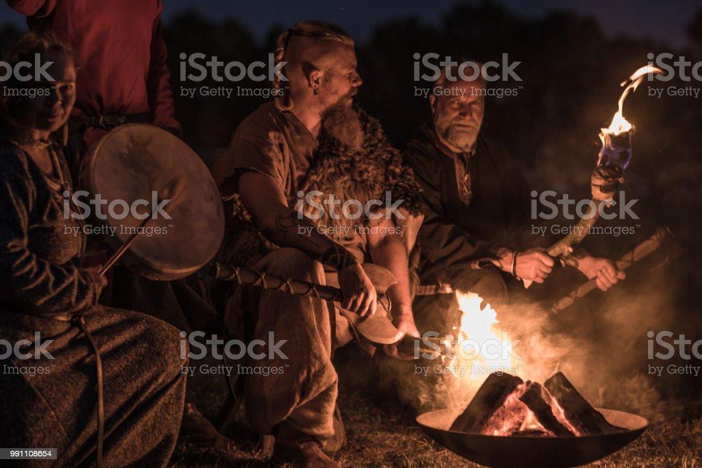 Uma horda de guerreiros Vikings sentado e falando ao redor de uma fogueira à noite - foto de acervo