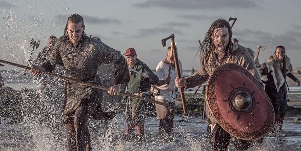 A hoard of Weapon wielding viking warriors fighting in a battlefield scene in the sea