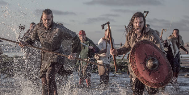 a hoard of weapon wielding viking warriors fighting in a battlefield scene in the sea - indumento corazzato foto e immagini stock
