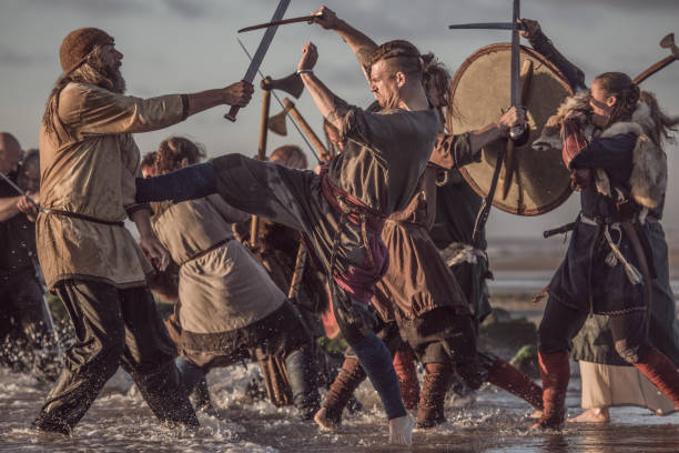 A hoard of Weapon wielding viking warriors fighting in a battlefield scene in the sea A hoard of Weapon wielding viking warriors fighting in a battlefield scene in the sea battlefield stock pictures, royalty-free photos & images