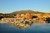 A view of Sullivans Harbor in Hobart, Tasmania on a clear day with Mt. Wellington rising in the background. The Broadcast Australia Tower, or NTA, sticks up on Mt. Wellington like a rocket poised for takeoff,