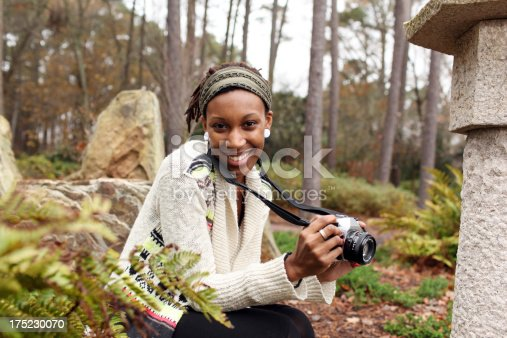 Teenage girl holding an old fashion SLR camera learning photography.