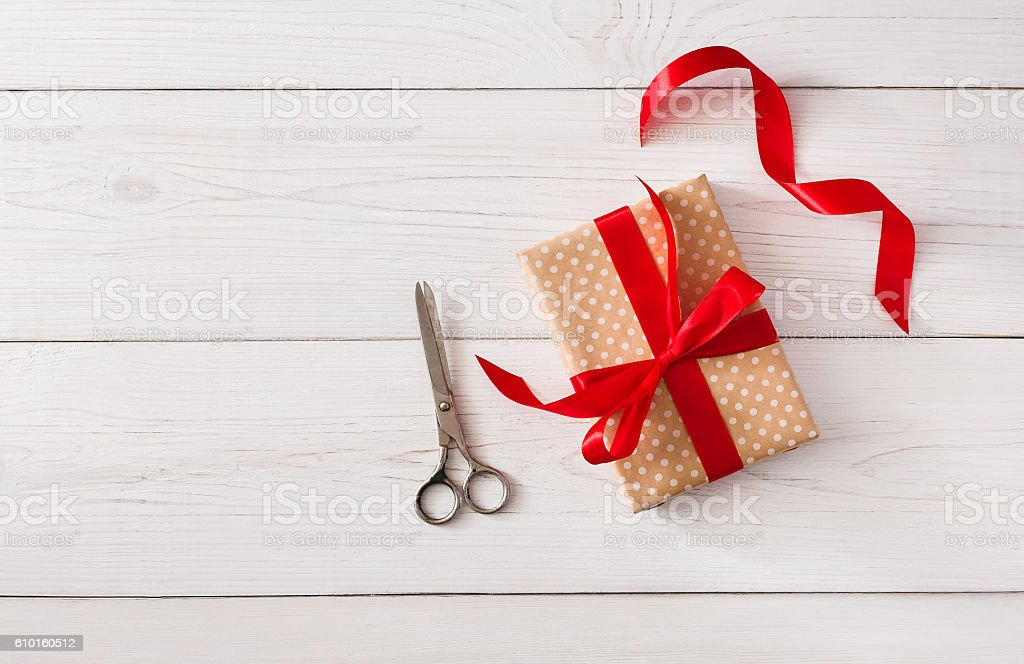 DIY hobby background. Making box for christmas present DIY hobby background. Making box for christmas or other holiday handmade present in craft paper with red ribbon. Scissors on white wooden table, top view with copy space Art And Craft Stock Photo