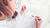 Hobby and leisure concept. Talent and creativity. Cropped shot of female artist drawing portrait on canvas.